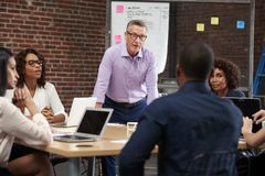 Hombre de negocios maduro Leading Office Meeting de los colegas que se sientan alrededor de la tabla imagen de archivo