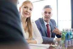 Hombre de negocios maduro que discute con los colegas en la mesa de reuniones en oficina Imagenes de archivo