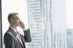 Hombre de negocios maduro que habla en el teléfono celular por la ventana imágenes de archivo libres de regalías