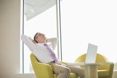 Hombre de negocios maduro que se relaja en pasillo Imagen de archivo libre de regalías