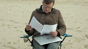 Hombre de negocios maduro que se sienta y que se relaja cerca de un río Hombre en una chaqueta y un ordenador portátil calientes  almacen de metraje de vídeo