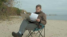 Hombre de negocios maduro que se sienta y que se relaja cerca de un río Hombre en una chaqueta y un ordenador portátil calientes  almacen de video