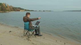 Hombre de negocios maduro que se sienta y que se relaja cerca de un río Hombre en una chaqueta y un ordenador portátil calientes  metrajes
