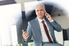 Hombre de negocios maduro serio que habla en el teléfono móvil en oficina Fotos de archivo libres de regalías