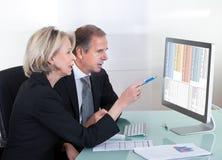 Hombre de negocios maduro y empresaria que miran el gráfico Fotografía de archivo