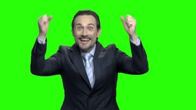 Hombre de negocios maduros hermoso que aumenta sus brazos en el entusiasmo metrajes