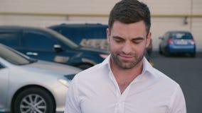 Hombre de negocios masculino acertado joven que camina con confianza a través del estacionamiento Retrato del hombre de negocios  metrajes
