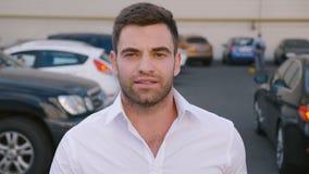 Hombre de negocios masculino acertado joven que camina con confianza a través del estacionamiento Retrato del hombre de negocios  almacen de metraje de vídeo