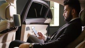 Hombre de negocios masculino joven que habla en el teléfono en el coche almacen de metraje de vídeo