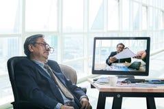 Hombre de negocios mayor asleeping en hora laborable de la oficina con el himse Imagen de archivo