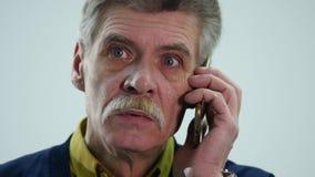 Hombre de negocios mayor chocado sobre las noticias que él recibe en su teléfono celular, fondo blanco almacen de metraje de vídeo