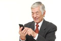 Hombre de negocios mayor con un teléfono elegante Foto de archivo