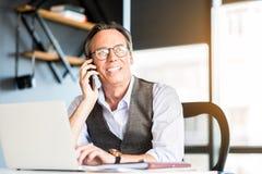 Hombre de negocios mayor confiado alegre que habla en el teléfono móvil Fotografía de archivo