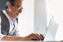 Hombre de negocios mayor confiado que se sienta en la tabla con el cuaderno Fotos de archivo libres de regalías