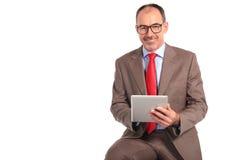 Hombre de negocios mayor confiado que trabaja en la tableta Imágenes de archivo libres de regalías