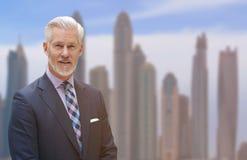 Hombre de negocios mayor delante de la ciudad grande Foto de archivo