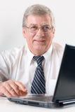 Hombre de negocios mayor en la computadora portátil, sonriendo fotografía de archivo libre de regalías