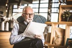 Hombre de negocios mayor en su comprobación de la oficina documentos imágenes de archivo libres de regalías