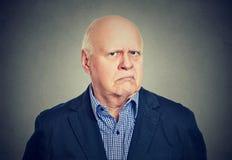 Hombre de negocios mayor enojado, gruñón, aislado en fondo gris foto de archivo libre de regalías