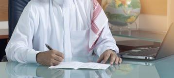 Hombre de negocios mayor Hand Writing At del saudí su escritorio imagenes de archivo