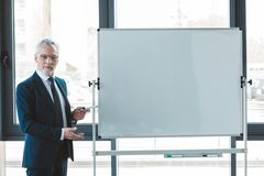 hombre de negocios mayor hermoso en lentes que señala en el whiteboard y la mirada en blanco foto de archivo