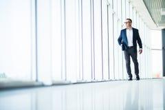 Hombre de negocios mayor hermoso y acertado que camina en interior moderno de la oficina imagenes de archivo