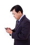 Hombre de negocios mayor infeliz que recibe malas noticias vía el smartphone app Foto de archivo libre de regalías