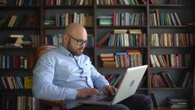 Hombre de negocios mayor positivo que trabaja en casa almacen de video