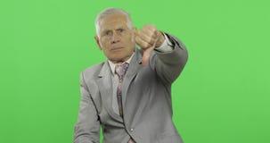 Hombre de negocios mayor que da el pulgar dow Viejo hombre en pulgar de la demostración del desgaste formal abajo metrajes