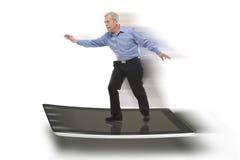 Hombre de negocios mayor que mantiene el equilibrio en una tablilla de la PC Imágenes de archivo libres de regalías