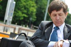 Hombre de negocios mayor que mira los relojes Foto de archivo