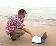 Hombre de negocios mayor que se sienta con el cuaderno en la playa Imagen de archivo libre de regalías