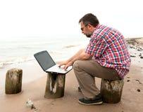 Hombre de negocios mayor que se sienta con el cuaderno en la playa Foto de archivo