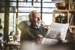 Hombre de negocios mayor que se sienta en su oficina, librando el ne foto de archivo libre de regalías