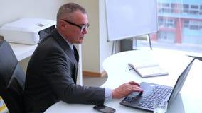 Hombre de negocios mayor que trabaja con el ordenador en oficina metrajes