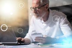 Hombre de negocios mayor que trabaja en el ordenador portátil, efecto luminoso, efecto luminoso, sobrepuesto con los diagramas imagenes de archivo