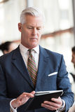 Hombre de negocios mayor que trabaja en la tableta Fotografía de archivo