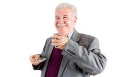 Hombre de negocios mayor sonriente con el té que mira hacia fuera Imágenes de archivo libres de regalías