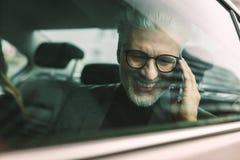 Hombre de negocios mayor sonriente que hace llamada de teléfono en taxi fotografía de archivo libre de regalías