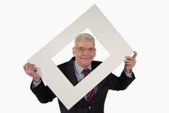 Hombre de negocios mayor sonriente que sostiene un montaje de la foto Imagenes de archivo