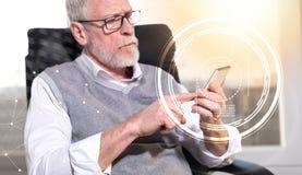 Hombre de negocios mayor usando su teléfono móvil, efecto luminoso, sobrepuesto con los diagramas foto de archivo