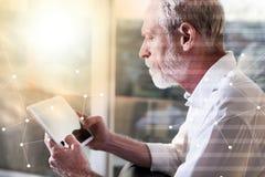 Hombre de negocios mayor usando una tableta digital, efecto luminoso, sobrepuesto con la red imagen de archivo libre de regalías