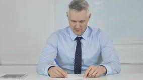 Hombre de negocios mayor Writing Letter en el trabajo, papeleo almacen de video