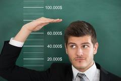 Hombre de negocios Measuring His Salary fotografía de archivo libre de regalías
