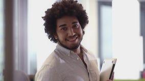 Hombre de negocios medio-oriental que usa la tableta en oficina metrajes