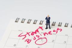Hombre de negocios miniatura con la confianza que se coloca en el calendario blanco con el círculo en negocio del comienzo de la  imagenes de archivo