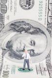 Hombre de negocios miniatura que se coloca en dólar de EE. UU. fotos de archivo libres de regalías