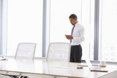 Hombre de negocios On Mobile Phone en la sala de reunión Foto de archivo