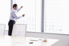 Hombre de negocios On Mobile Phone en la sala de reunión Imagen de archivo