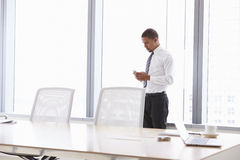 Hombre de negocios On Mobile Phone en la sala de reunión Imagenes de archivo